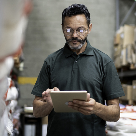 man standing and doing work on a tablet