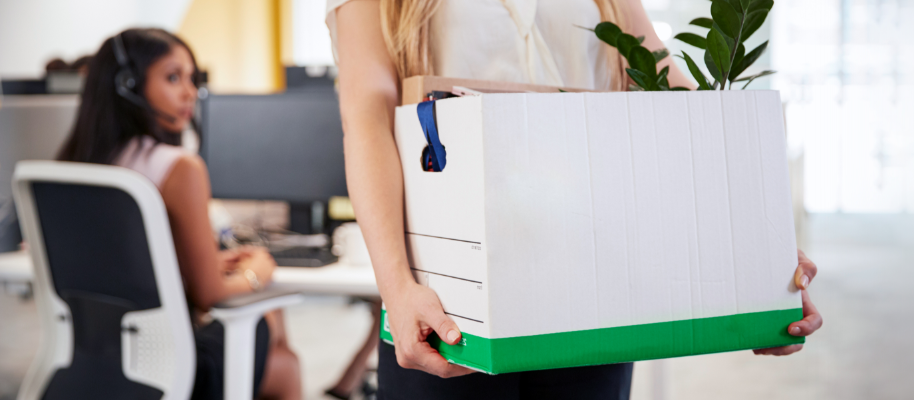 woman carrying box after clearing off her work desk